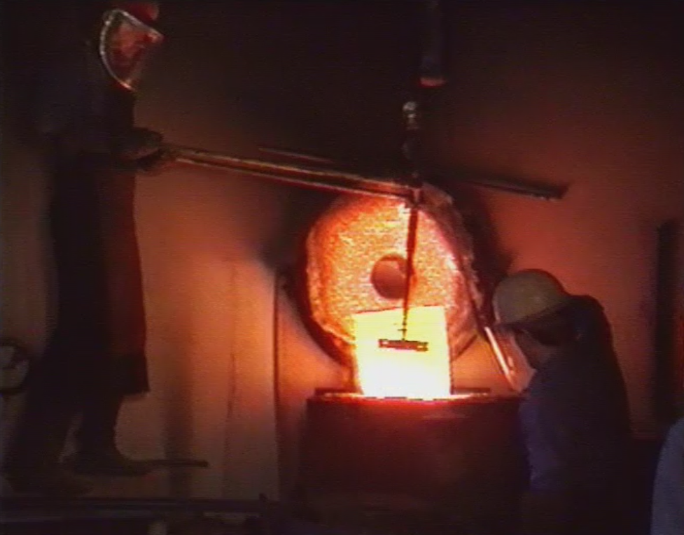The metal has been melted in a graphite crucible, which is seen here being removed from the kiln