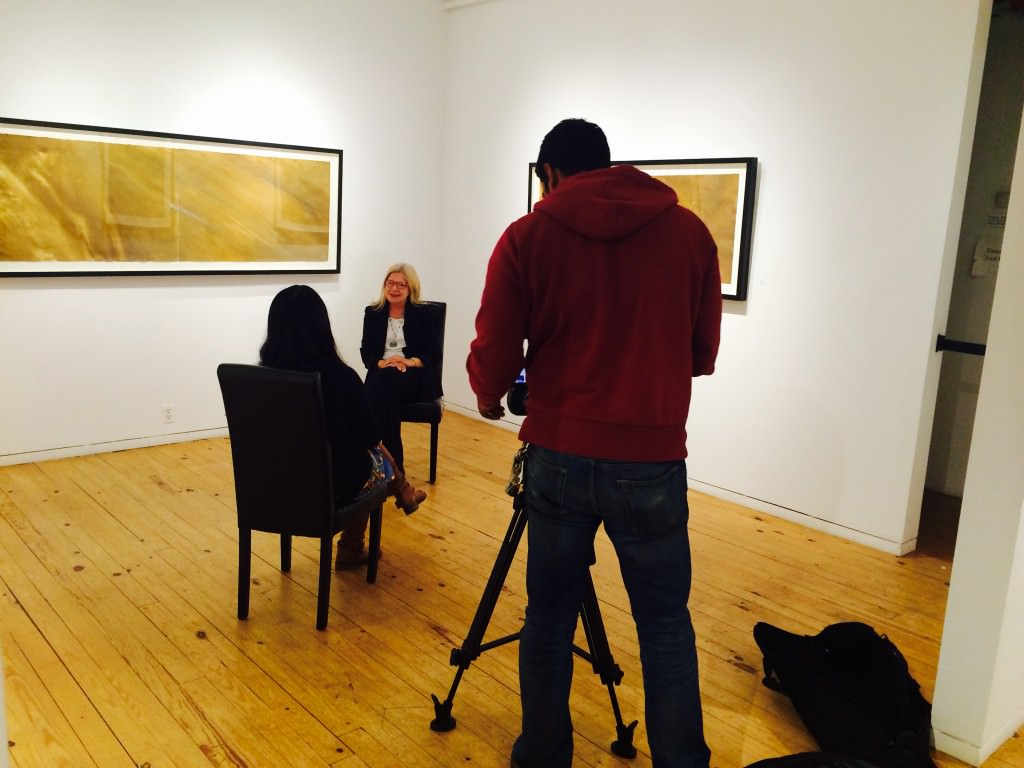 Gallery Director, Angela Di Bello, being interviewed by Michael Lam's large-scale watercolors.
