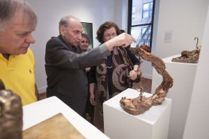 Artist Loukas Tsevdos showing his bronze sculpture, Rebirth to guests at the Agora Gallery opening reception