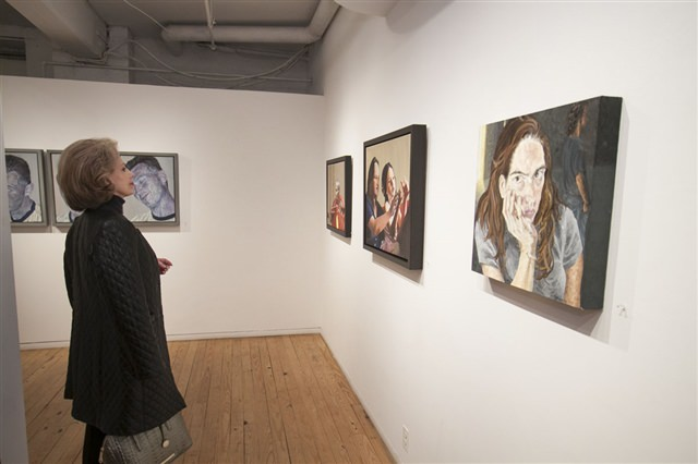 Visitor looking at Lucy O'Donovan's Paintings in her March exhibition, Mélange of Milieu