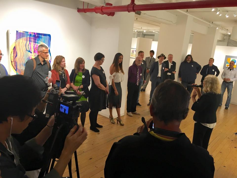 Gallery Director Angela Di Bello speaking with the exhibiting artists before the reception