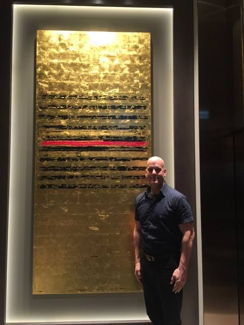 David Stanley Hewett with one of his works in the sixth floor lobby of The Oakwood Premier Tokyo