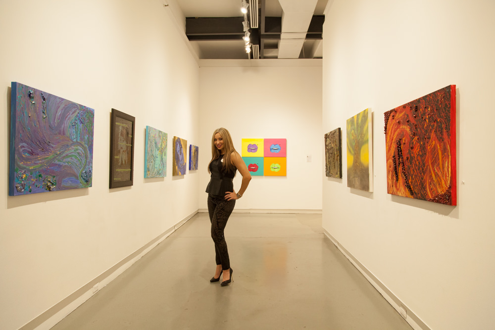 Artist JCK poses among her paintings at Agora Gallery at the opening reception